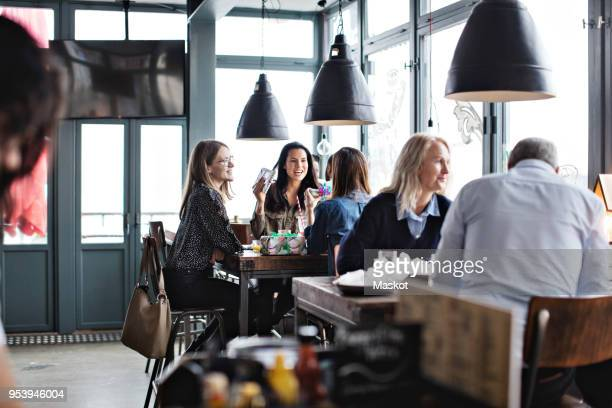 customers enjoying while sitting at restaurant - restaurant stock photos and pictures