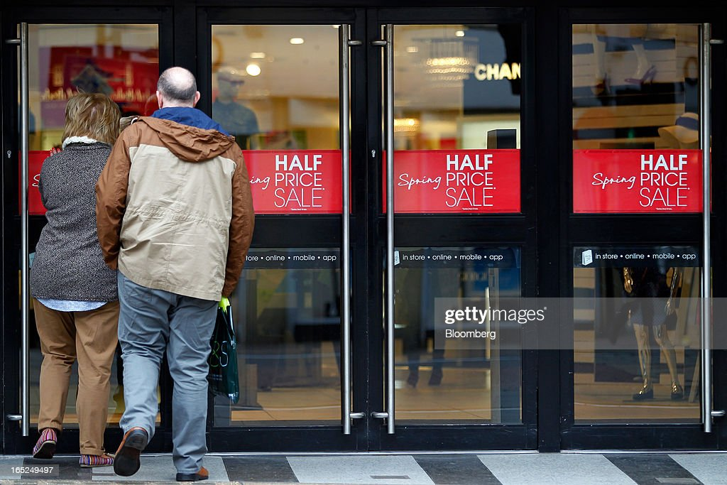 Customers enter a Debenhams Plc department store advertising a half price sale in central Manchester, U.K., on Monday, April 1, 2013. U.K. retail sales unexpectedly stagnated in March in a sign that consumer spending remains under pressure from higher energy bills and weak wage growth. Photographer: Paul Thomas/Bloomberg via Getty Images