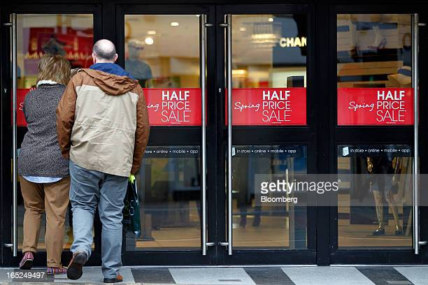 Customers enter a Debenhams Plc department store advertising a half price sale in central Manchester UK on Monday April 1 2013 UK retail sales...