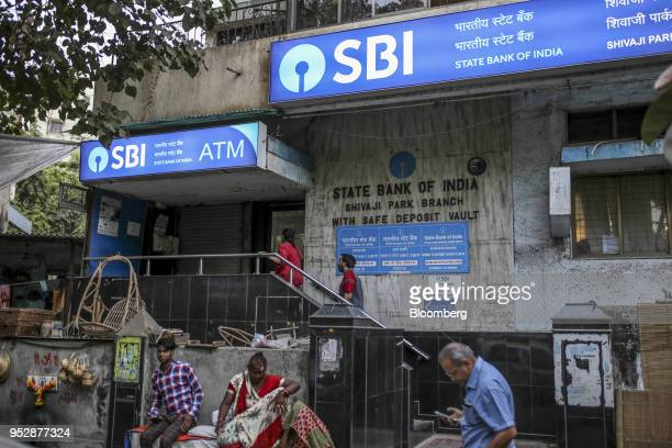 Customers enter a State Bank of India Bank branch in Mumbai India on Saturday April 21 2018 State Bank of India is scheduled to announce full year...