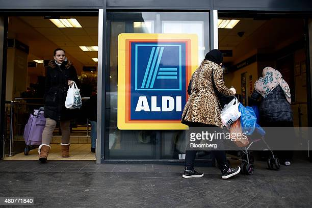 Customers enter and exit an Aldi Stores Ltd supermarket in the Kilburn district of London UK on Monday Dec 22 2014 German discounters Aldi and Lidl...