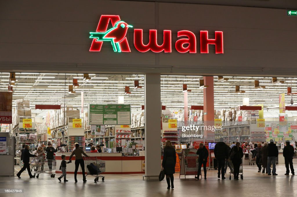 Customers enter and exit an Auchan Groupe SA store at the MEGA Belaya Dacha shopping complex, constructed by the real estate development arm of Inter Ikea Systems BV and one of Europe's largest malls, in Moscow, Russia, on Thursday, Jan. 31, 2013. Russian shopping-mall construction may climb to a record this year as retailers take advantage of rising sales by moving into bigger, more modern buildings, Cushman & Wakefield Inc. said. Photographer: Andrey Rudakov/Bloomberg via Getty Images