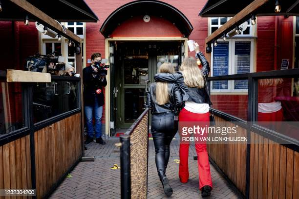 Customers enter Cafe De Beurs in Utrecht on April 14 as part of an experiment to open cafes in a safe way in an attempt to limit the spread of the...
