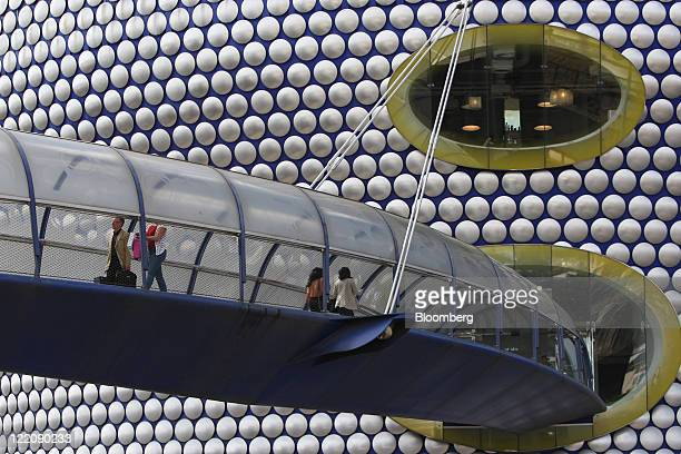 Customers enter the Selfridges Co department store by aerial walkway at the Bullring shopping center operated by Hammerson Plc in Birmingham UK on...