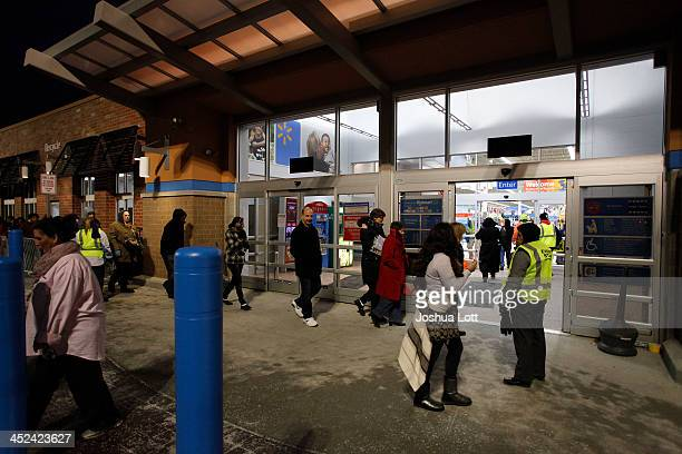 Customers enter WalMart Thanksgiving day after waiting in line on November 28 2013 in Troy Michigan Black Friday shopping began early this year with...