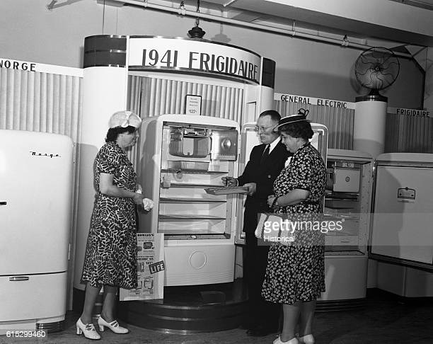 Customers examine a new electric refrigerator in the CrowleyMilner department store Detroit Michigan July 1941