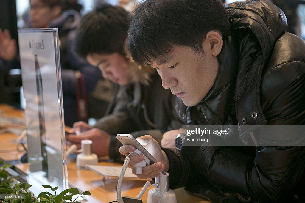 Customers examine the Apple Inc. iPhone 5 at a KT Corp. Olleh brand mobile phone store in Seoul, South Korea, on Friday, Dec. 7, 2012. The iPhone 5 went on sale in South Korea today. Photographer: Jean Chung/Bloomberg via Getty Images
