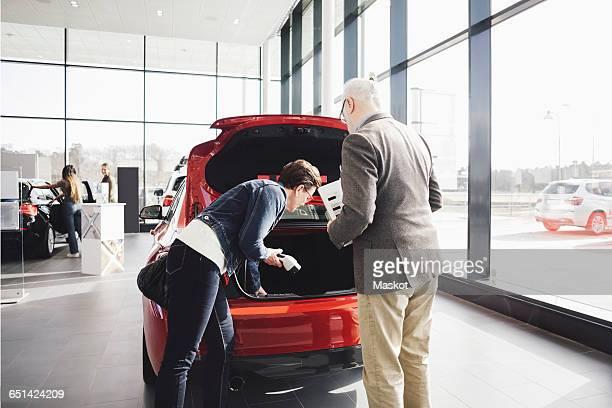 Customers examining car at showroom