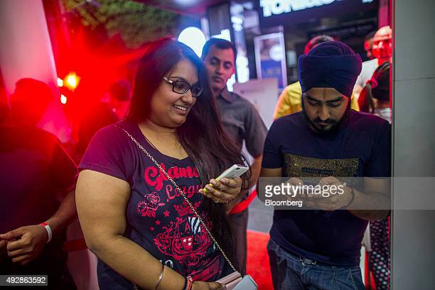 Customers exchange photos on Apple Inc iPhones as they wait in line outside an iZenica store operated by Zenica LifestylePvt prior to a midnight...