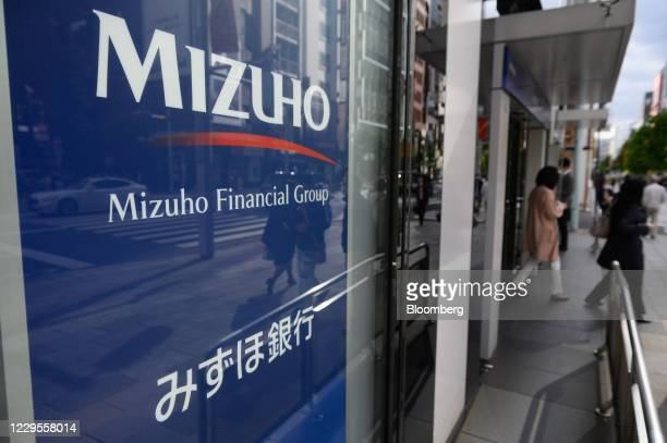 Customers exit a branch of Mizuho Bank Ltd. In Tokyo, Japan, on Monday, Nov. 9, 2020. Japanese banks expect business opportunities from...