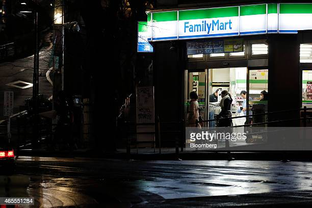 Customers exit a FamilyMart Co convenience store at night in Tokyo Japan on Saturday March 7 2015 FamilyMart and Uny Group Holdings Co are in merger...