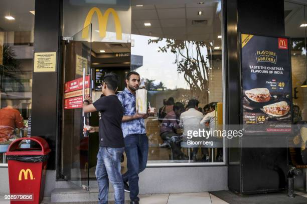 Customers exit a McDonald's Corp restaurant operated by Hardcastle Restaurants Pvt in Mumbai India on Tuesday March 20 2018 As the world's largest...