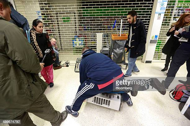 Customers fall to the floor as they grapple for an LED television during a Black Friday discount sale at an Asda supermarket operated by WalMart...