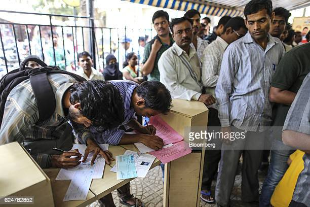 Customers fill in forms as other customers wait in line to withdraw cash at a State Bank of India branch in Mumbai India on Saturday Nov 19 2016...