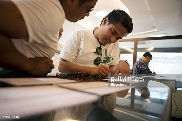Customers fill in slips inside a Civil Bank Ltd branch in Kathmandu Nepal on Thursday May 28 2015 Nepal's gross domestic product will probably grow...