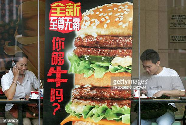 Customers finish their meal at a branch of McDonalds in Beijing 20 June 2006 The US fastfood giant said it will open about two stores a week in China...