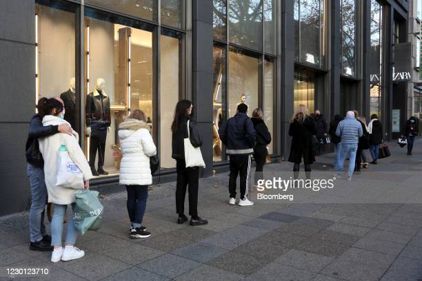 Customers form a social distanced queue to enter a Zara clothing store, operated by Inditex SA, in Berlin, Germany, on Monday, Dec. 14, 2020. Germany...