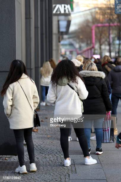 Customers form a social distancing queue to enter a Zara clothing store, operated by Inditex SA, in Berlin, Germany, on Monday, Dec. 14, 2020....