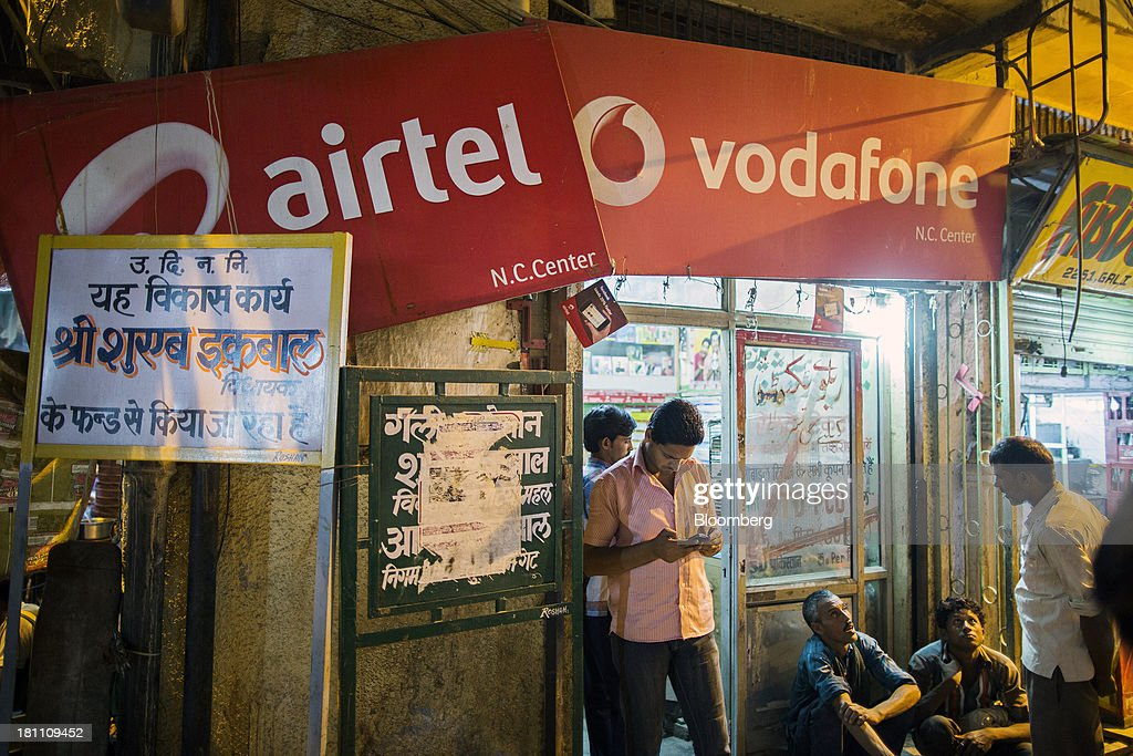Customers gather outside a multi-brand mobile phone store displaying signage for Bharti Airtel Ltd. and Vodafone Group Plc in the old Delhi area of New Delhi, India, on Wednesday, Sept. 18, 2013. The Federal Reserves decision to postpone its rollback of U.S. stimulus offered Asian policy makers extra time to address domestic economic fragilities as the region copes with diminished capital inflows. Photographer: Prashanth Vishwanathan/Bloomberg via Getty Images