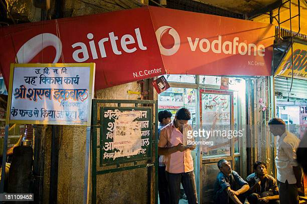 Customers gather outside a multibrand mobile phone store displaying signage for Bharti Airtel Ltd and Vodafone Group Plc in the old Delhi area of New...
