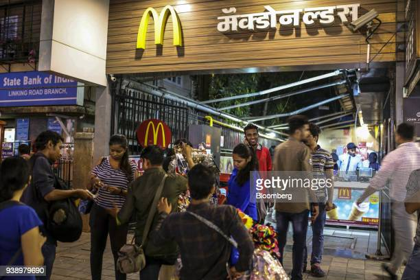 Customers gather outside after leaving a McDonald's Corp restaurant operated by Hardcastle Restaurants Pvt in Mumbai India on Tuesday March 20 2018...