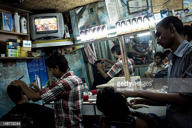 Customers get a shave in a barber shop in Kotla Mubarakpur New Delhi India on Thursday Aug 2 2012 A series of failures and excessive demand on the...