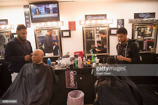 Customers get their hair cut at the Prime Time Barber and Beauty shop on West Florissant Street November 15 2014 in Ferguson Missouri Business has...