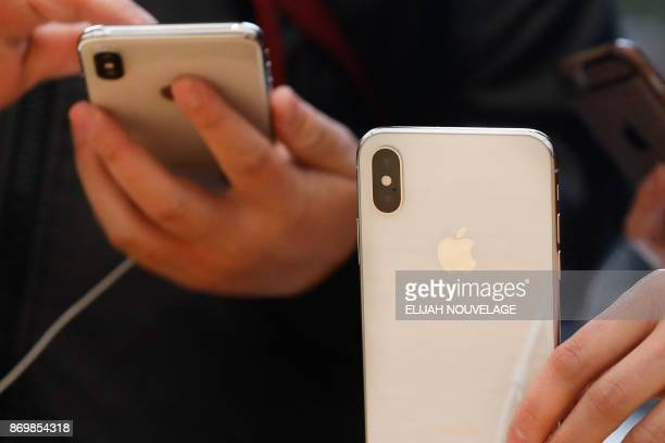 Customers handle the new iPhone X at the Apple Store Union Square on November 3 in San Francisco California Apple's iPhone X hit stores around the...