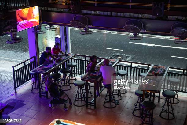 Customers have a drink at a near-empty bar during a rainstorm in Patong, Phuket, Thailand, on Saturday, Dec. 19, 2020. The tepid response to...
