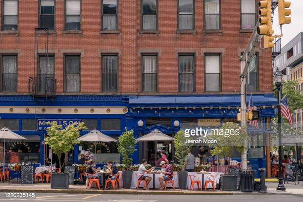 Customers have a lunch outside a restaurant as the city reopens from the coronavirus lockdown on June 15, 2020 in Hoboken, New Jersey. The state has...