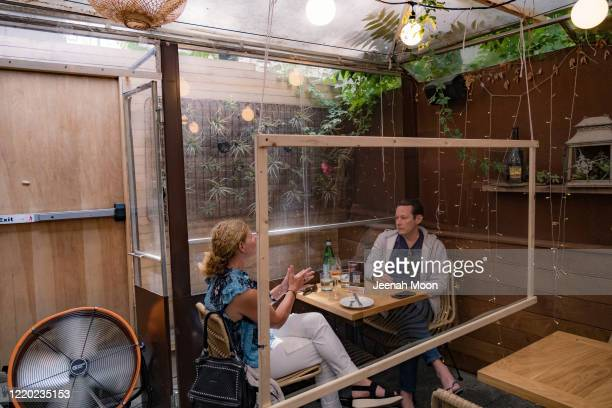Customers have lunch at a restaurant with social distancing measures in place as the city reopens from the coronavirus lockdown on June 15, 2020 in...