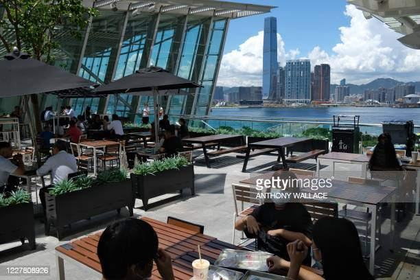 Customers have lunch at an outdoor dining area of a shopping mall in Hong Kong on July 28 a day before new social distancing measures come into...