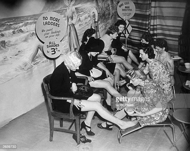 Customers have their legs painted at a store in Croydon, so they can save their coupons which would otherwise be used for stockings.