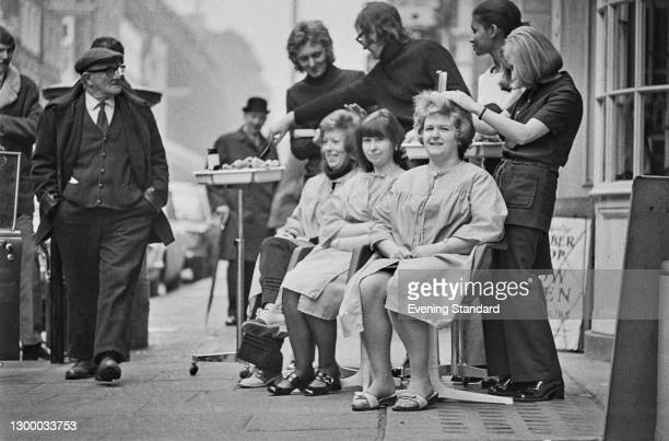 Customers having their hair cut on the pavement in Hatton Garden, London, due to power cuts following a miners' strike, UK, 17th February 1972.