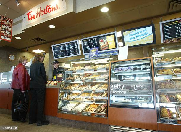 Customers Heather Arnfinson left and Kim O'Brien wait for their order at a Calgary Alberta Canada Tim Hortons store March 7 2006 Canadians who eat...