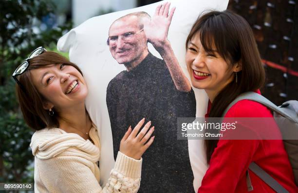 Customers hold a pillow with an image of the late Apple Inc cofounder Steve Jobs as they wait in line before the launch of the iPhone X outside the...