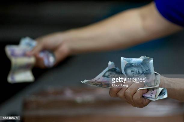 Customers hold Chinese yuan banknotes while shopping inside a wet market in the Sanlitun area of Beijing China on Saturday Sept 13 2014 Chinese...