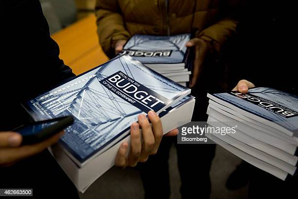 Customers hold copies of US President Barack Obama's Fiscal Year 2016 Budget while waiting in line to purchase the books at the US Government...