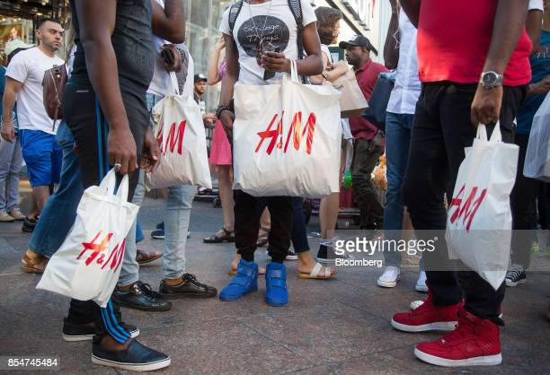 Customers hold Hennes Mauritz AB shopping bags outside a store in New York US on Saturday Sept 23 2017 Hennes Mauritz AB is scheduled to release...