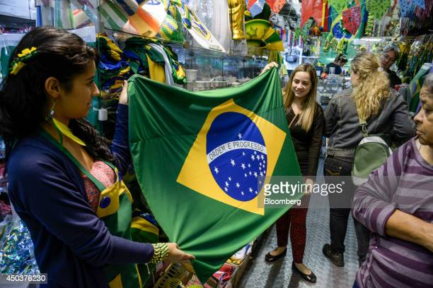 Customers hold up a Brazilian flag at a shop on Rua 25 de Marco, in Sao Paulo, Brazil, on Saturday, June 7, 2014. Tourists from the Netherlands to...