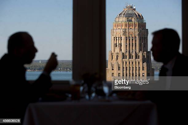 Customers Horace Jioia, left, and Ed Graber eat lunch at the Mid-Day Club of Buffalo as Buffalo City Hall stands in the background in Buffalo, New...