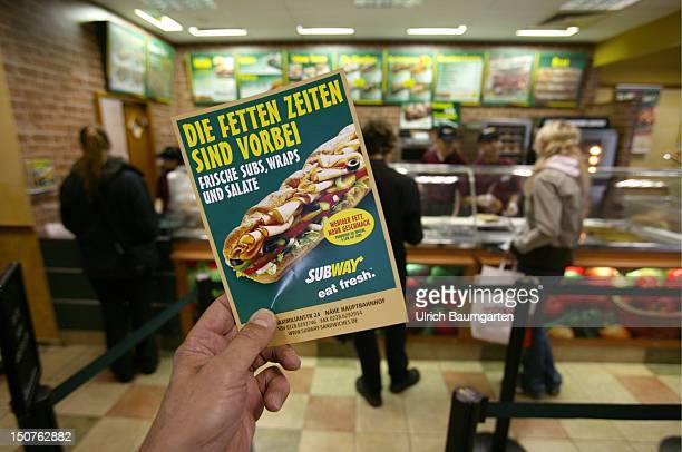 Customers in a branch of the US American sandwich fastfood chain Subway In the front an advertising leaflet