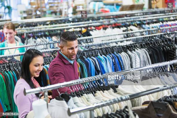 Customers in a thrift shop, rows of shirts