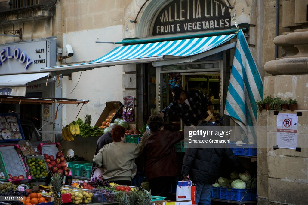 Customers in front of a fruit and vegetables store in St. Christopher's Street on December 9, 2017 in Valletta, Malta. Valletta, a fortified town that dates back to the 16th century, is the southernmost capital of Europe and a UNESCO World Heritage Site: together with all the Maltese islands, it will be hosting the title of European Capital of Culture in 2018.