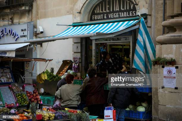 Customers in front of a fruit and vegetables store in St Christopher's Street on December 9 2017 in Valletta Malta Valletta a fortified town that...