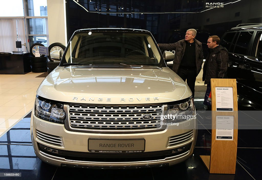 Customers inspect a new Range Rover automobile on display in an independent auto showroom in Moscow, Russia, on Friday, Dec. 28, 2012. Tata Motors Ltd.'s Jaguar Land Rover luxury unit signed a letter of intent with Saudi Arabia's government to study the feasibility of setting up a factory to build its models locally. Photographer: Andrey Rudakov/Bloomberg via Getty Images