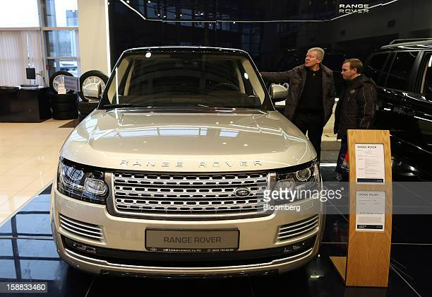 Customers inspect a new Range Rover automobile on display in an independent auto showroom in Moscow Russia on Friday Dec 28 2012 Tata Motors Ltd's...