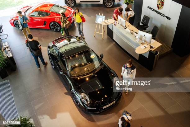 Customers inspect a Porsche 911 Carrera vehicle inside a Porsche SE showroom in Singapore on Sunday June 4 2017 Singapores economy may be picking up...