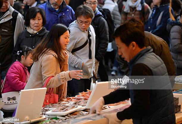 Customers inspect fresh fish for sale at Ameyoko market in Tokyo Japan on Saturday Dec 26 2015 Photographer Japans consumer prices rose slightly in...