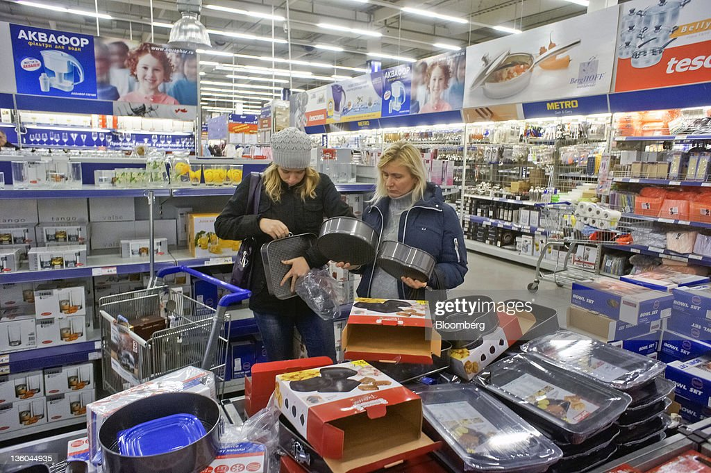 Customers inspect kitchen goods for sale at a Metro Cash ...